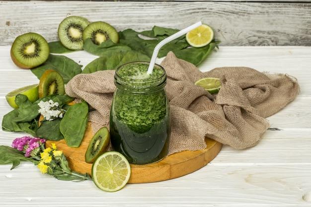 Frullato verde in un barattolo con lime e frutti di bosco Foto Gratuite