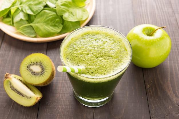 Frullato verde sano con kiwi, mela sul tavolo di legno rustico Foto Premium
