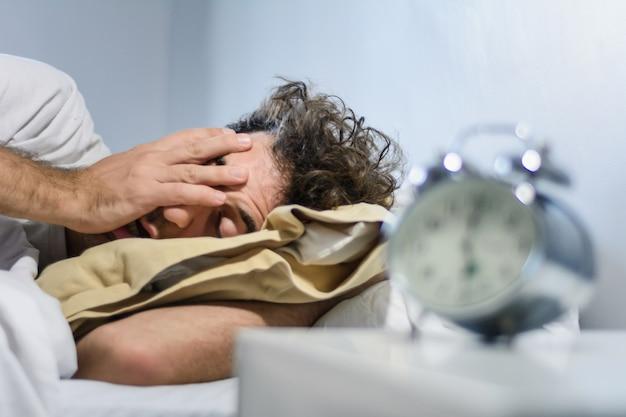 Frustrato giovane svegliato dalla sua sveglia Foto Premium
