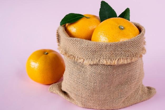 Frutta arancione succosa fresca messa sopra rosa-chiaro Foto Gratuite