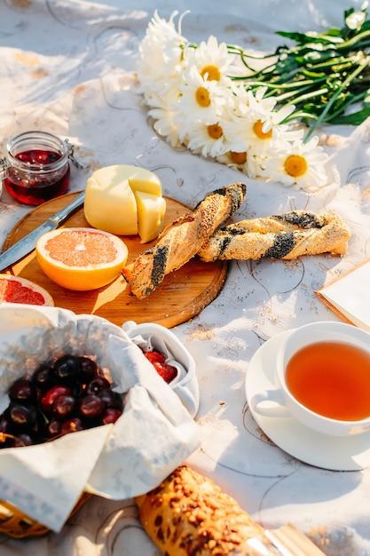Frutta, cornetti, marmellata, tè e fiori sulla tovaglia alla luce del sole estivo. concetto di pic-nic Foto Premium