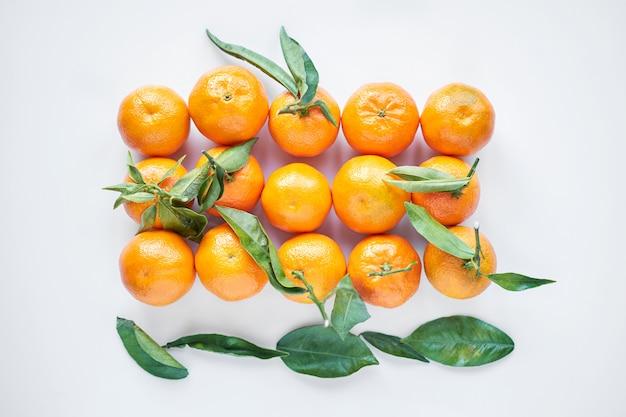 Frutta di natale. i mandarini o i mandarini freschi arancio con le foglie verdi in un sacco di carta si trovano su un fondo bianco. Foto Premium