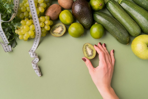Frutta e verdura piana di disposizione con il kiwi della tenuta della mano Foto Gratuite