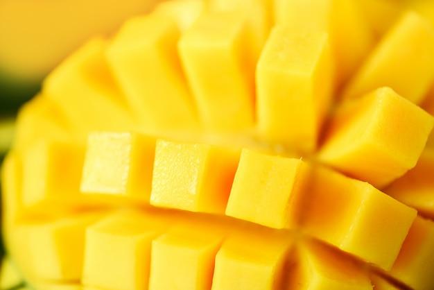 Frutta esotica del mango sopra le foglie di palma verdi tropicali su fondo giallo. pop art design, concept creativo estivo. Foto Premium