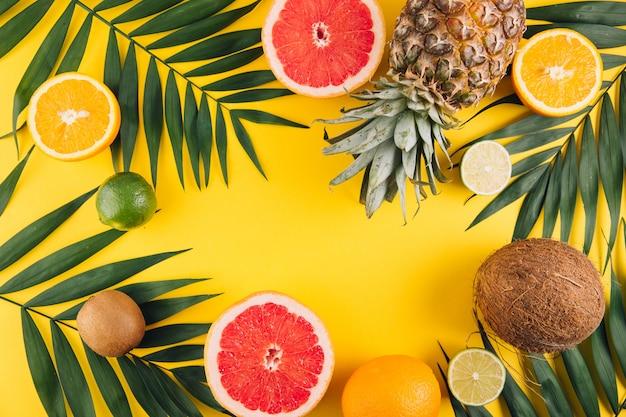 Frutta estiva foglie di palma tropicale, ananas, cocco, pompelmo, arancia e lime su sfondo giallo. Foto Premium