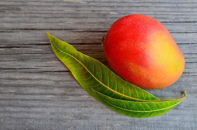 Frutta fresca del mango e foglie dell'albero di mango su legno Foto Premium