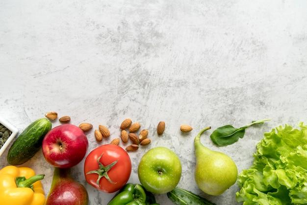 Frutta fresca e sana; verdure e mandorle su superficie strutturata in cemento bianco Foto Gratuite