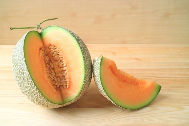 Frutta fresca matura di melone con un pezzo di frutta a fette su un tavolo di legno Foto Premium