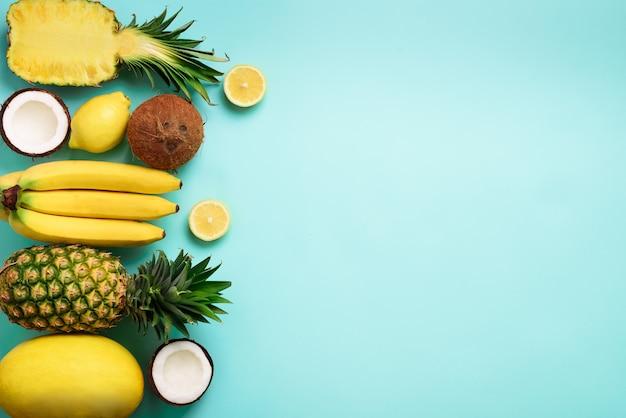 Frutta gialla organica fresca sopra priorità bassa blu. concetto monocromatico con banana, cocco, ananas, limone, melone. Foto Premium