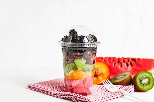 Frutta in un bicchiere di plastica. Foto Premium