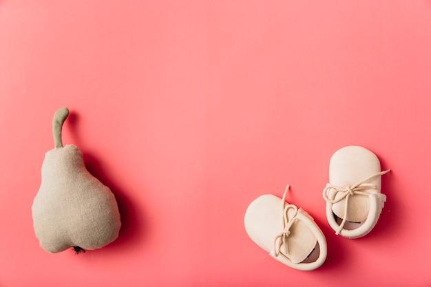 Frutta pera farcita e paio di scarpe per bambini su sfondo colorato Foto Gratuite