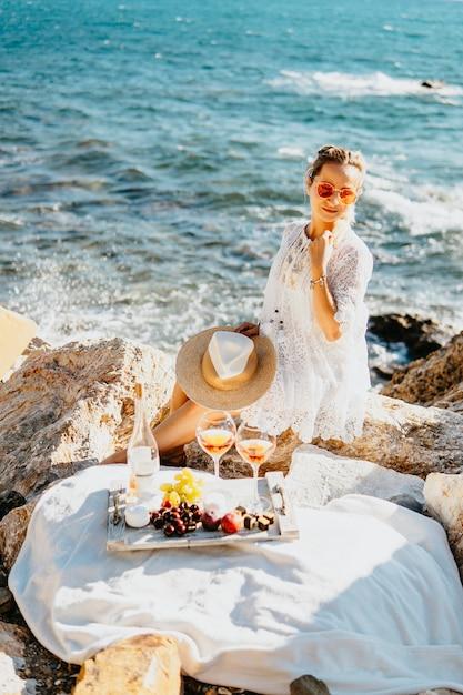 Frutta, snack e bevande durante il picnic in mare. ragazza che fa la farina di mais sul lato mare con rocce, vestita in abito elegante bianco, cappello di paglia. concetto di viaggio di turismo agricolo. viaggia nei paesi del sud Foto Premium
