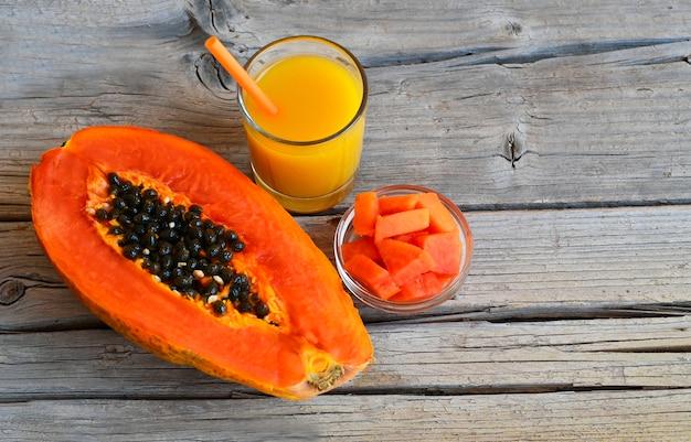 Frutta tropicale organica matura fresca della papaia con un bicchiere di succo Foto Premium
