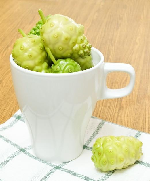 Frutta verde noni o morinda citrifolia in tazza bianca Foto Premium