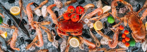 Frutti di mare sul ghiaccio. granchi, storioni, molluschi, gamberetti, rapana, dorado, su ghiaccio bianco. Foto Premium