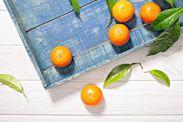 Frutti freschi del mandarino con le foglie sulla cassa di legno Foto Premium