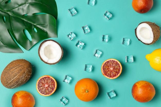 Frutti tropicali, arance rosse, cocco, foglia di palma Foto Premium