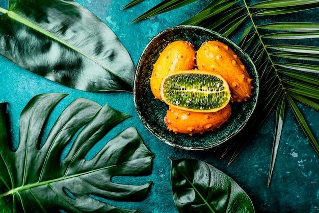 Frutto tropicale kiwano frutto della passione in una ciotola verde su turchese con foglie di palma tropicale. vista dall'alto. tropicale Foto Premium