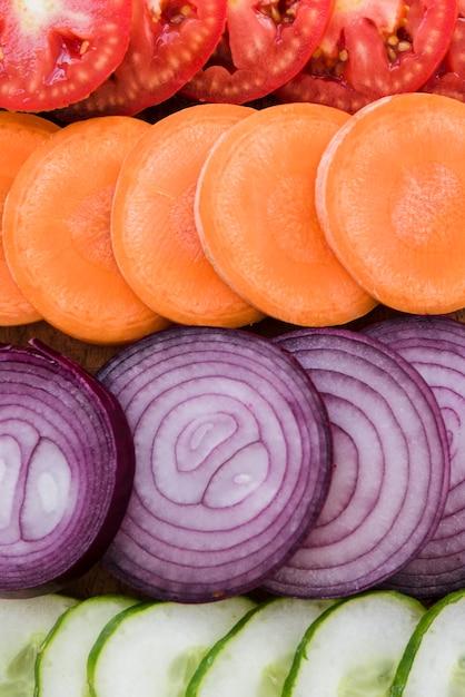 Full frame di pomodori; carota; sfondo di fette di cipolla e cetriolo Foto Gratuite