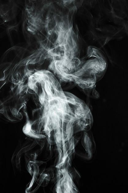 Fumo trasparente bianco che soffia su sfondo nero Foto Gratuite