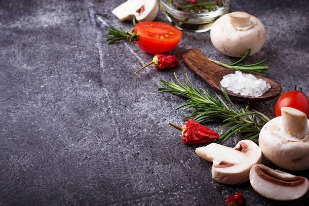 Funghi, pomodori, rosmarino, sale e olio. sfondo di cibo messa a fuoco selettiva Foto Premium