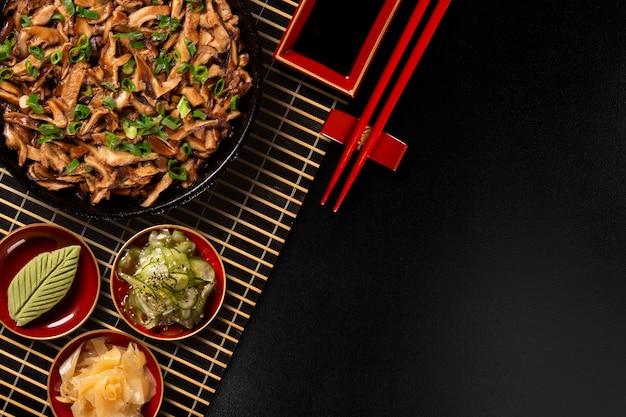 Funghi shimeji in padella di ferro con zenzero, wasabi e sunomono in uno sfondo nero. vista dall'alto. Foto Premium