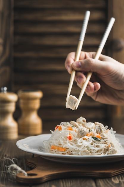 Fungo asiatico delle tagliatelle dell'alimento con il pollo ed i bastoni per alimento su legno con copyspace Foto Premium