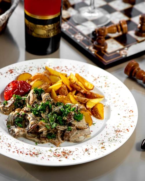 Fungo cremoso condito con erbe e patate fritte Foto Gratuite