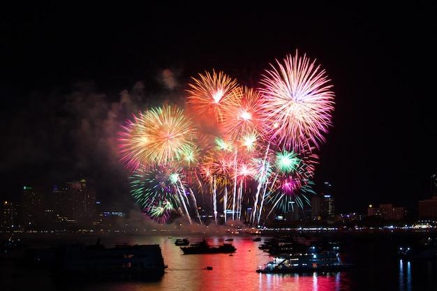 Fuochi d'artificio arcobaleno finale sulla spiaggia e il colore di riflessione sulla superficie dell'acqua Foto Premium