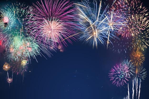 Fuochi d'artificio variopinti sul fondo del cielo nero sopra-acqua Foto Premium