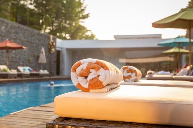 Fuoco selettivo al portasciugamani sul letto della spiaggia intorno alla piscina in hotel. Foto Premium