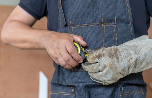 Fuoco selettivo dell'uomo del carpentiere con nastro adesivo di misurazione a disposizione, concetto dell'artigiano. Foto Premium