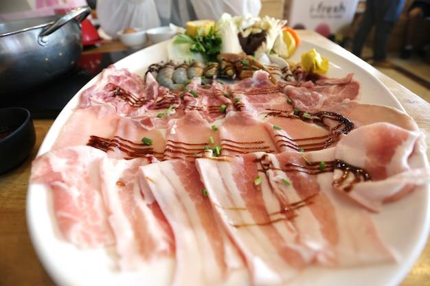 Fuoco selettivo di carne di maiale affettata fresca cruda con le verdure per cucinare o shabu shabu e sukiyaki, alimento giapponese Foto Premium