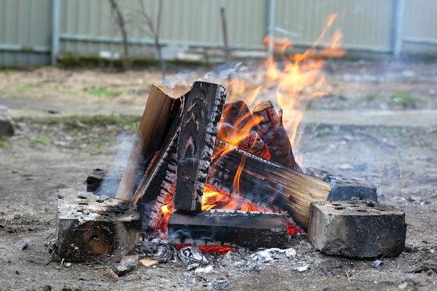 Fuoco sulla natura. legna da ardere in fiamme all'aperto. Foto Premium