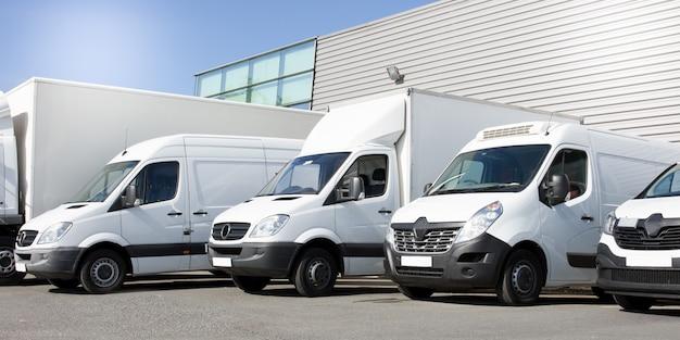 Furgoni bianchi di consegna in camion e auto di servizio davanti all'ingresso di una società logistica di distribuzione di magazzino Foto Premium