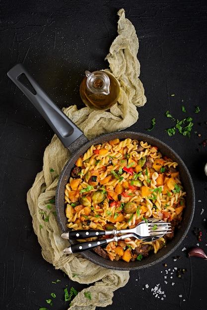 Fusilli di pasta vegetale con zucca, cavoletti di bruxelles, paprika e pezzi di fegato. vista dall'alto Foto Premium