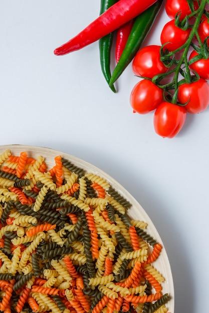 Fusilli pasta in un piatto con pomodori, peperoni piatto giaceva su un tavolo bianco Foto Gratuite