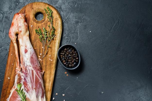 Gamba cruda di capra su un tagliere di legno. rosmarino, timo, pepe nero. Foto Premium