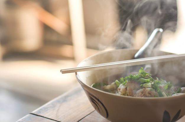 Gamba di maiale in umido con la tagliatella sulla tavola di legno, cibo tailandese Foto Premium