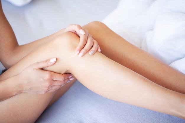 Gambe della donna sollevate sul bagaglio, giovane donna a casa sdraiata a letto. la camera bianca Foto Premium