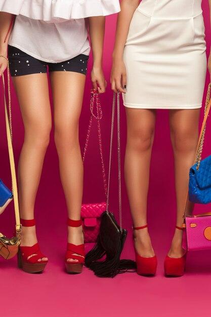 Gambe di moda sul muro rosa Foto Premium