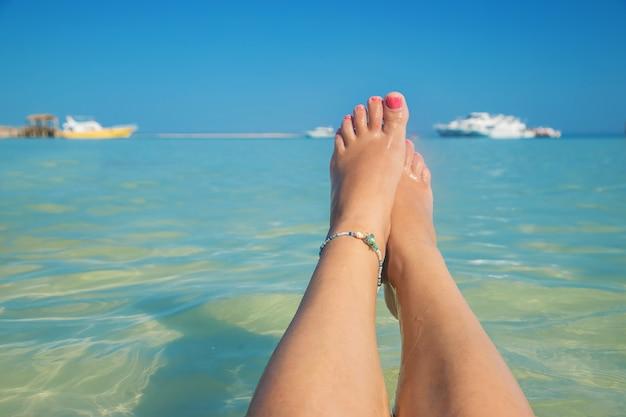 Gambe di una ragazza in riva al mare Foto Premium