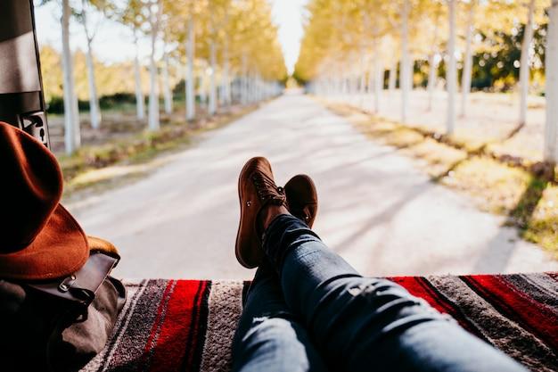 Gambe sveglie del cane e della donna di jack russell che si rilassano in un furgone. concetto di viaggio. messa a fuoco selettiva sugli alberi Foto Premium