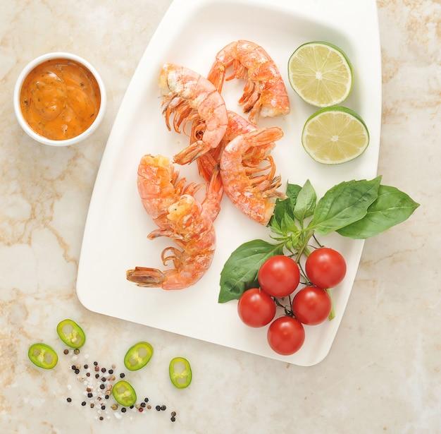 Gamberi alla griglia con basilico e pomodorini su un piatto bianco Foto Premium