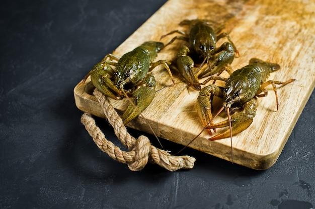 Gamberi vivi su un tagliere di legno. Foto Premium