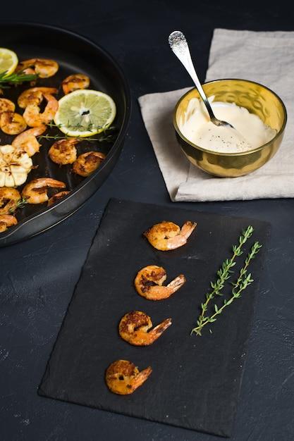 Gamberoni fritti in padella su un nero con una ciotola di salsa. Foto Premium