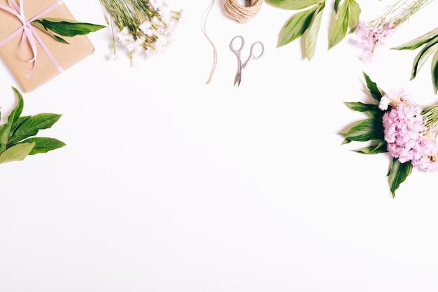 Garofani fiori, regali, nastri e carta da imballaggio su un tavolo bianco Foto Premium