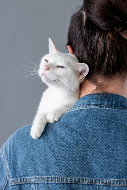 Gatto bianco che si siede sulla spalla del proprietario Foto Gratuite