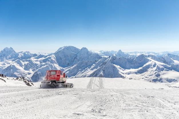 Gatto delle nevi su un pendio in alto nelle montagne Foto Premium