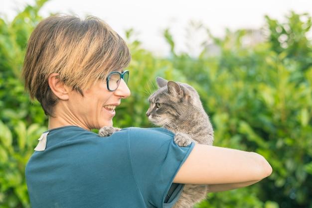 Gatto domestico allegro tenuto e coccolato dalla donna sorridente con gli occhiali. Foto Premium